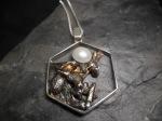 Pendentif hexagonal en argent sterling oxydé et orné d'une perle cultivée.