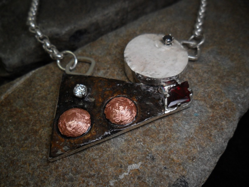 Collier jouant sur la géométrie, en argent sterling, orné d'un grenat taiilé en losange et serti de diamants blanc et noir sur chaton en or 14K.